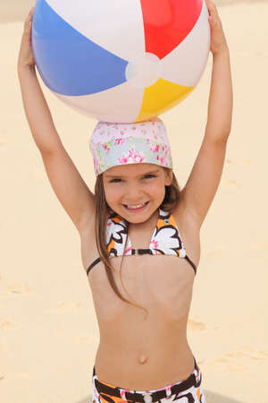 Little at the beach holding inflatable ball above head photo