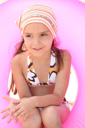 Young girl in bikini sitting in an inflatable beach ring photo