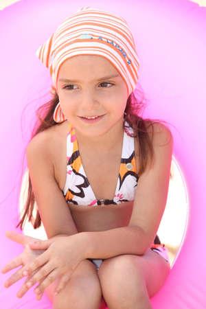 Young girl in bikini sitting in an inflatable beach ring photo