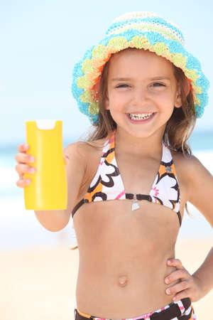 child in bikini: Little girl on the beach with cream
