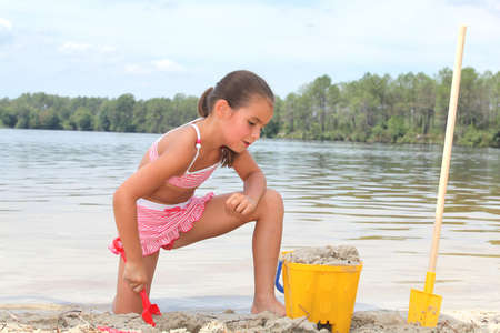 beach front: Young girl building sandcastles on the beach Stock Photo