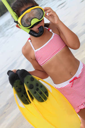 animal masks: little girl on the beach wearing swimsuit and having diving apparatus Stock Photo