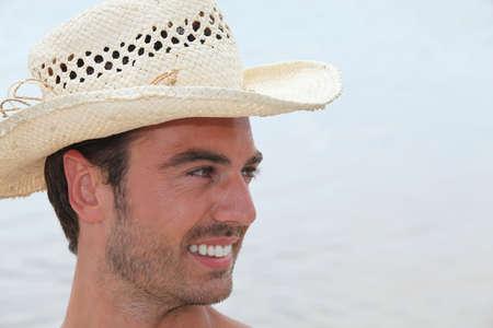 chapeau de paille: jeune homme avec un chapeau de paille posant dans le profil