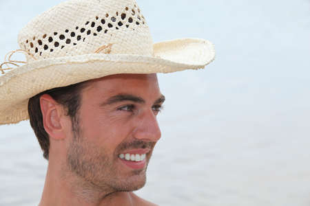 young man with straw hat posing in profile Stock Photo - 13974344