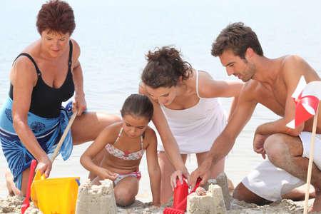 Family making sandcastle photo