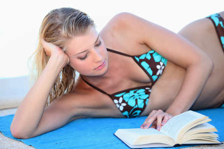 Blond woman reading a book whilst sunbathing photo
