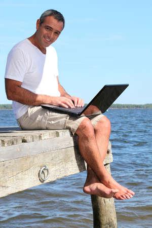 Mann mit einem Laptop im Urlaub Standard-Bild - 13959432