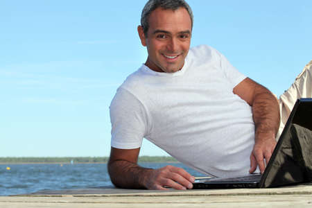 hairy arms: Man looking his laptop by the lake