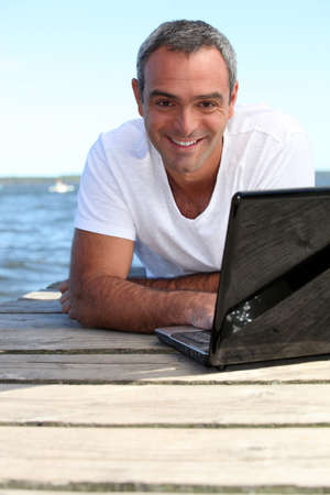 Man using his laptop on a wooden jetty photo