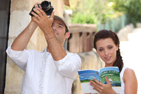 Couple of tourists with camera and guide book Stock Photo - 13962446