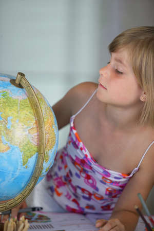 little girl looking at a globe photo