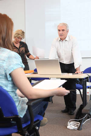 evening class: Teacher stood at the front of the classroom
