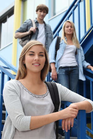 Three students standing on an exterior staircase photo