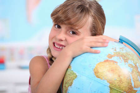 Young girl hugging a globe photo