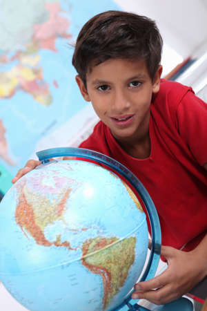 school age boy: Little boy looking at a globe