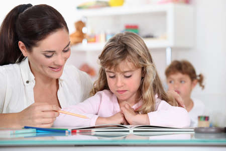 Primary school teacher with young girl Stock Photo - 13960237
