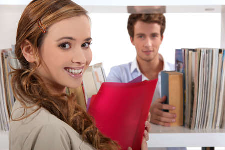 Couple flirting in a library Stock Photo - 13961992