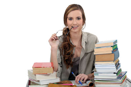 Female student sat at desk with books photo
