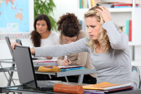counterparts: female student using laptop in class at college Stock Photo