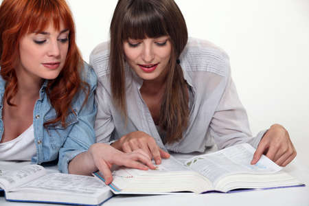language dictionary: Young women looking up a word in the dictionary