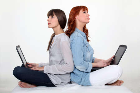 Two female friends sat together each using a laptop computer Stock Photo - 13962243