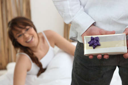 gift behind back: Man bringing gift to his girlfriend Stock Photo