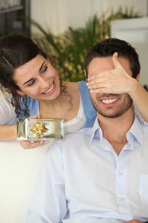 Woman giving gift to boyfriend photo