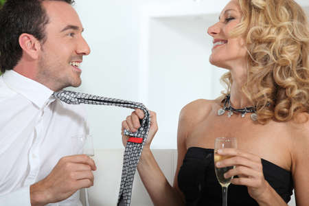 seducing: Woman drinking champagne whilst grabbing mans tie