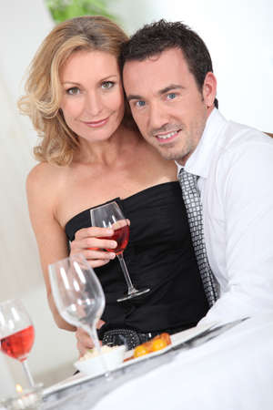 hugging knees: Couple with a glass of wine