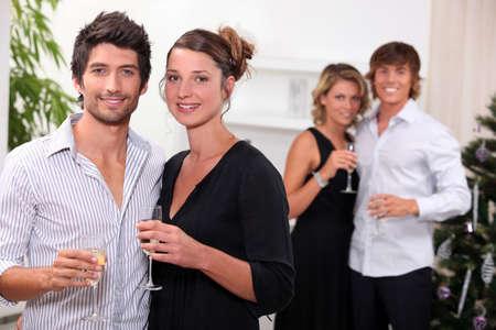 brindisi champagne: Due coppie festeggiano il Natale Archivio Fotografico