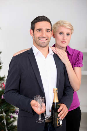 Couple drinking champagne by Christmas tree photo