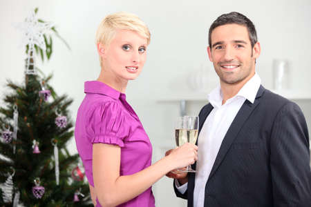 Couple drinking champagne in front of a christmas tree photo