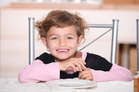 little girl smiling at table for afternoon snack photo
