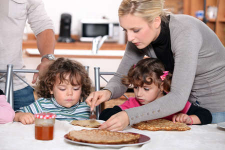 Parents preparing breakfast for children photo