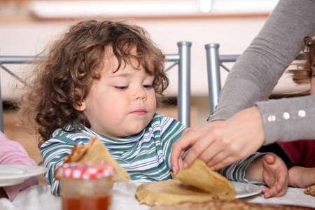 ni�os desayuno: Madre dar a los ni�os el desayuno Foto de archivo