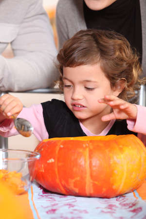 Little girl carving pumpkin photo