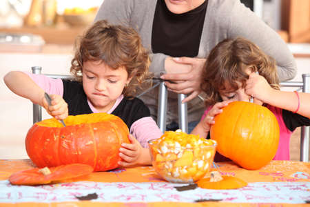 scooping: Children carving halloween pumpkins Stock Photo