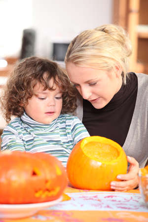 Mother and son carving pumpkin photo