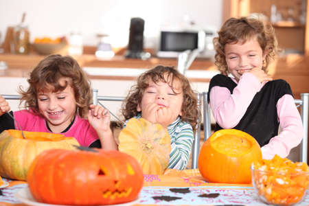 chuckling: Giggling girls carving pumpkins