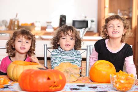 Three children with pumpkins photo