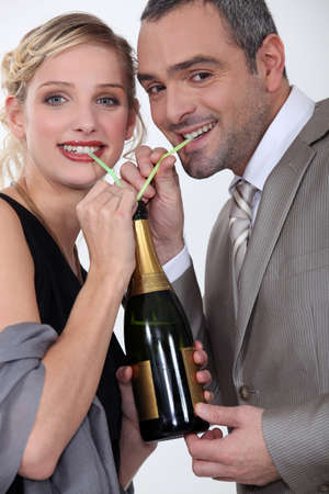Couple drinking champagne through straw photo