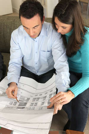 Couple examining a blueprint photo