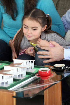 Girl looking at scale model of future home photo