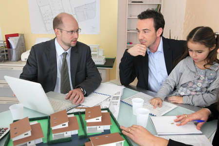 Architect and family discussing house plans photo