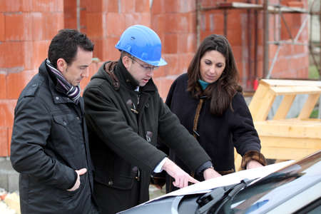 Architect reviewing a building plan with his clients photo