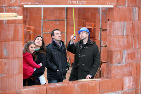 family and contractor on construction site photo