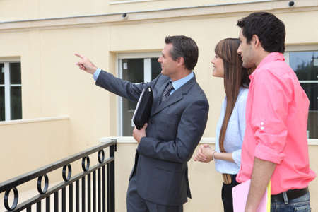 agents: couple and realtor showing property