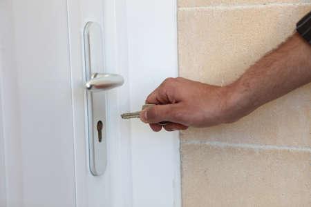 doorkey: Man putting a key in his front door