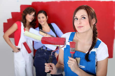 Three female friends painting wall photo