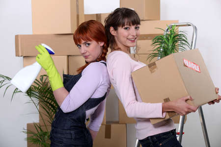 moving out: Young women cleaning out their apartment on moving day Stock Photo
